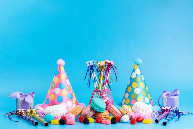Widok Z Przodu Francuskie Makaroniki Kolorowe Wraz Z Cukierkami I Zabawnymi Czapkami Na Niebiesko Darmowe Zdjęcia