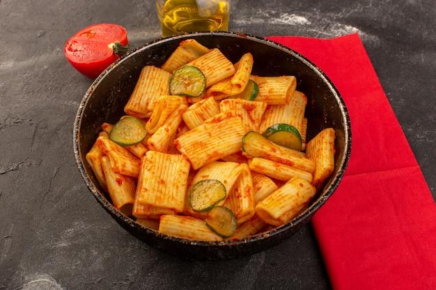 Widok Z Przodu Gotowanego Włoskiego Makaronu Z Sosem Pomidorowym I Ogórkiem Wewnątrz Patelni Na Ciemnym Biurku Darmowe Zdjęcia