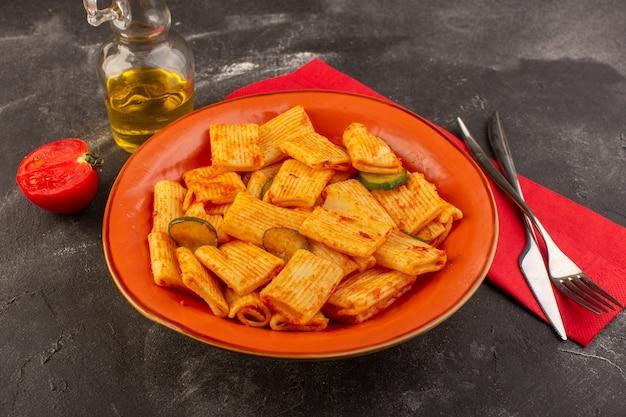 Widok Z Przodu Gotowanego Włoskiego Makaronu Z Sosem Pomidorowym I Ogórkiem Wewnątrz Płyty Na Ciemnej Powierzchni Darmowe Zdjęcia