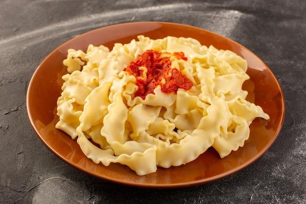 Widok Z Przodu Gotowanego Włoskiego Makaronu Z Sosem Pomidorowym Wewnątrz Płyty Na Szarej Powierzchni Darmowe Zdjęcia