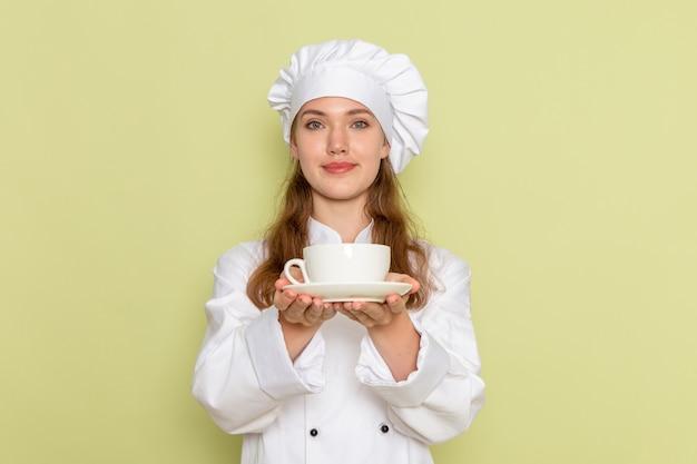 Widok Z Przodu Kobieta Kucharz W Białym Garniturze, Trzymając Kawę Na Zielonej ścianie Darmowe Zdjęcia