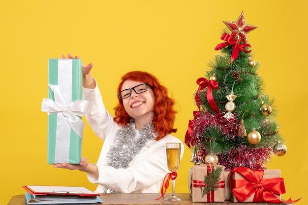 Widok Z Przodu Kobieta Lekarz Siedzi Z Prezentami świątecznymi I Drzewem Na żółtym Tle Darmowe Zdjęcia
