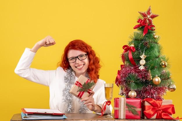 Widok Z Przodu Kobieta Lekarz Siedzi Za Stołem Z Prezentami świątecznymi Na żółtym Biurku Darmowe Zdjęcia