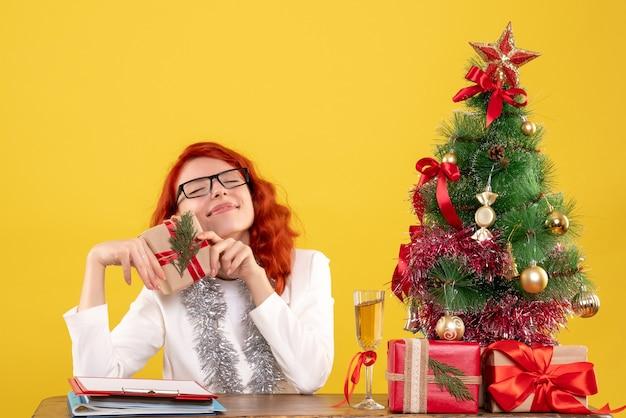 Widok Z Przodu Kobieta Lekarz Siedzi Za Stołem Z Prezentami świątecznymi Na żółtym Tle Z Choinką I Pudełkami Darmowe Zdjęcia