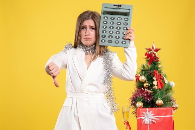 Widok Z Przodu Kobieta Lekarz Stojący I Trzymając Kalkulator Na żółtym Tle Z Choinką I Pudełkami Na Prezenty Darmowe Zdjęcia