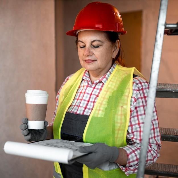 Widok Z Przodu Kobieta Pracownik Budowlany Z Kawą I Planem Darmowe Zdjęcia