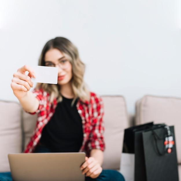 Widok z przodu kobieta trzyma kartę siedząc na kanapie Darmowe Zdjęcia