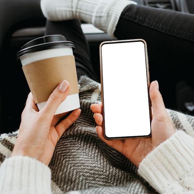 Widok Z Przodu Kobieta Trzyma Pusty Telefon I Filiżankę Kawy Darmowe Zdjęcia