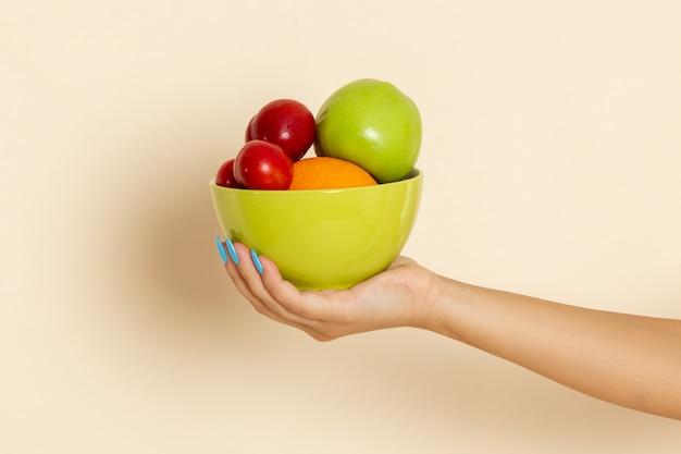Widok Z Przodu Kobieta Trzyma Talerz Z Różnymi Owocami Na Beżu Darmowe Zdjęcia