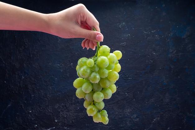 Widok Z Przodu Kobieta Trzyma Winogrona Na Ciemnoniebieskim Darmowe Zdjęcia