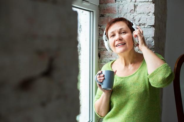 Widok z przodu kobieta w oknie słuchania muzyki Darmowe Zdjęcia