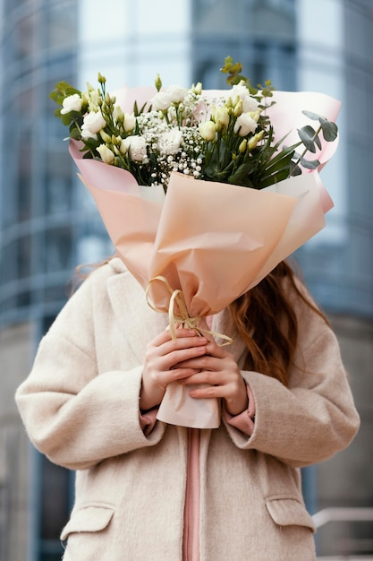 Widok Z Przodu Kobiety Trzymającej Bukiet Kwiatów Przed Jej Twarzą Na Zewnątrz Premium Zdjęcia