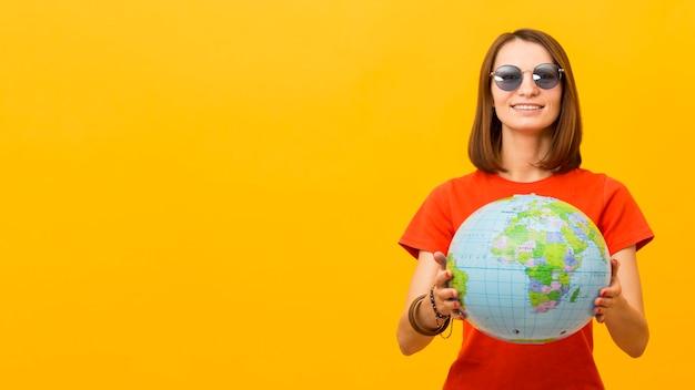 Widok Z Przodu Kobiety Trzymającej Kulę Ziemską Z Miejsca Na Kopię Z Okularami Przeciwsłonecznymi Darmowe Zdjęcia