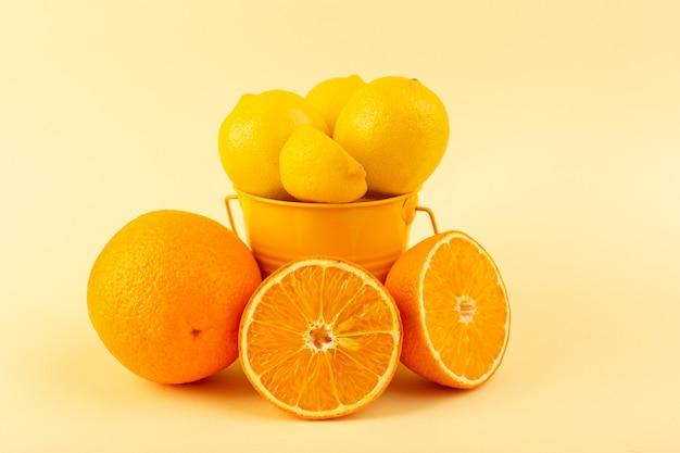 Widok Z Przodu Kosz Z Cytrynami Pokrojonymi W Całości, świeży Mellow I Soczysty Wraz Z Pomarańczowymi Plasterkami Na Kremowym Tle Darmowe Zdjęcia