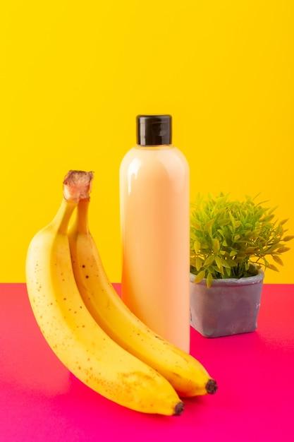 Widok Z Przodu Kremowy Szampon W Butelce Z Tworzywa Sztucznego Z Czarną Nakrętką Izolowaną Bananami I Małą Roślinką Na Różowo-żółtym Tle Kosmetyki Pielęgnacja Włosów Darmowe Zdjęcia