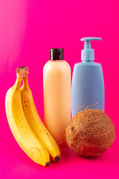 Widok Z Przodu Kremowy Szampon Z Plastikowej Butelki Z Czarną Nakrętką Izolowaną Wraz Z Bananową Niebieską Rurką I Orzechami Kokosowymi Na Różowym Tle Kosmetyki Pielęgnacja Włosów Darmowe Zdjęcia