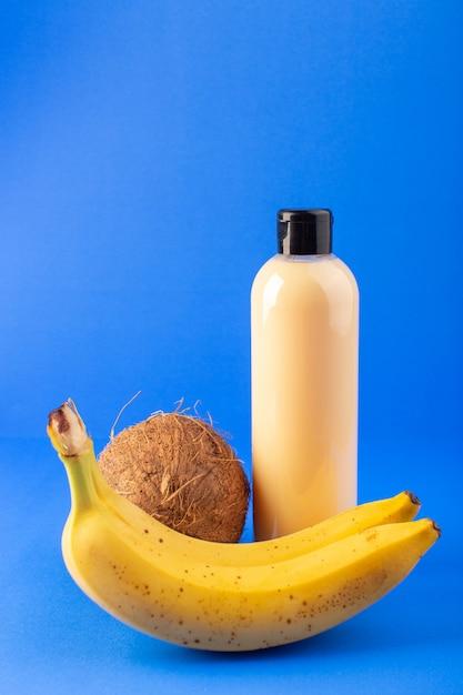 Widok Z Przodu Kremowy Szampon Z Plastikowej Butelki Z Czarną Nakrętką Izolowaną Wraz Z Kokosem I Bananami Na Niebieskim Tle Kosmetyki Pielęgnacja Włosów Darmowe Zdjęcia