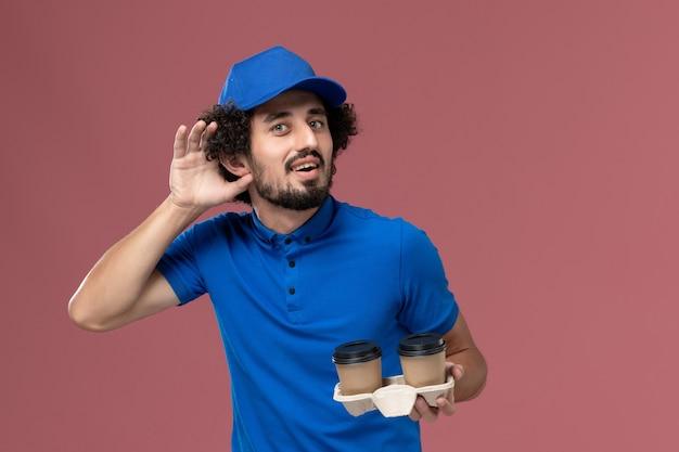 Widok Z Przodu Kuriera W Niebieskim Mundurze I Czapce Z Filiżankami Kawy Na Rękach, Próbując Usłyszeć Na Różowej ścianie Darmowe Zdjęcia