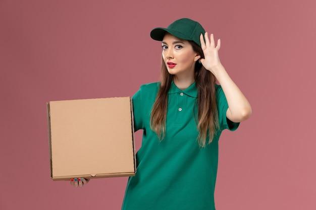 Widok Z Przodu Kurierka W Zielonym Mundurze Trzymająca Pudełko Z Jedzeniem Próbująca Usłyszeć Na Różowej ścianie Służba Pracy Jednolita Dostawa Pracy Darmowe Zdjęcia