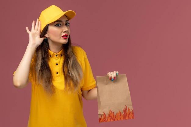 Widok Z Przodu Kurierki W żółtym Mundurze I Czapce Trzymającej Paczkę Z Jedzeniem Na Jasnoróżowej ścianie Darmowe Zdjęcia