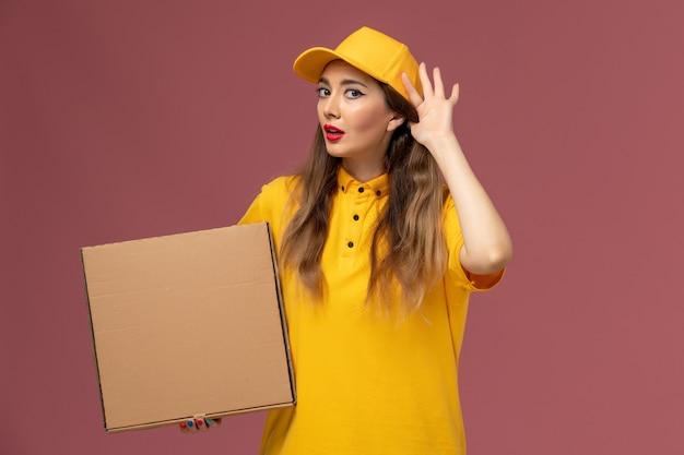 Widok Z Przodu Kurierki W żółtym Mundurze I Czapce Trzymającej Pudełko Z Jedzeniem, Próbującej Usłyszeć Na Jasnoróżowej ścianie Darmowe Zdjęcia
