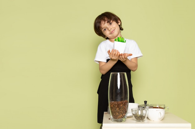 Widok Z Przodu ładny Chłopiec Uśmiecha Się Z Małą Zieloną Roślinę W Pobliżu Stołu Z Kawą I Filiżankami Na Kamiennej Kolorowej Podłodze Darmowe Zdjęcia
