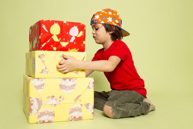 Widok Z Przodu ładny Chłopiec W Czerwonej Koszulce Trzyma Prezenty Na Kamiennej Przestrzeni Darmowe Zdjęcia