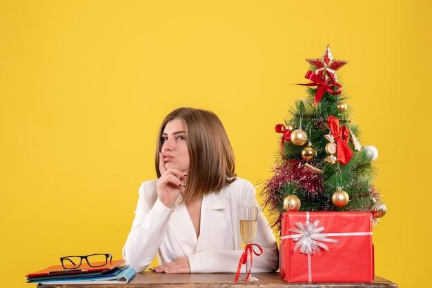Widok Z Przodu Lekarz Kobieta Siedzi Przed Stołem Z Prezentami święta I Drzewa Na żółtym Tle Darmowe Zdjęcia