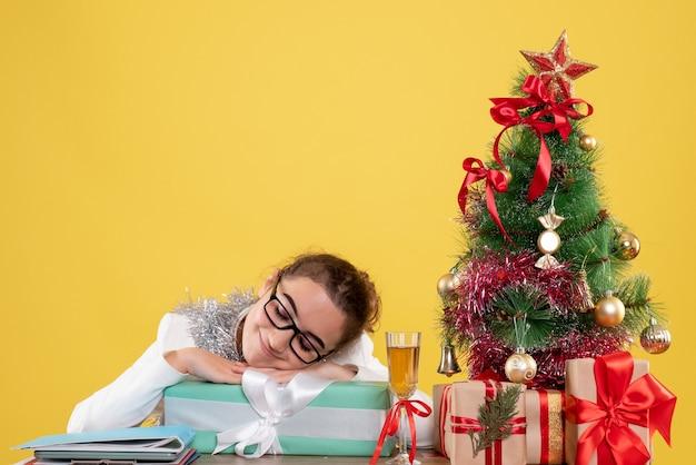 Widok Z Przodu Lekarz Kobieta Siedzi Wokół Prezentów świątecznych I Drzewa Na żółtym Tle Darmowe Zdjęcia