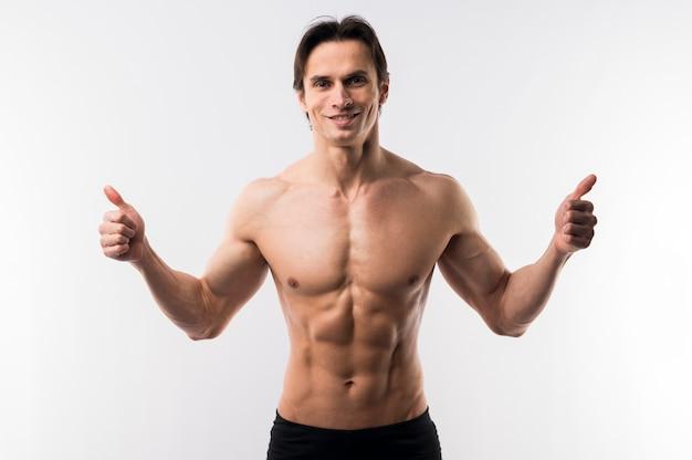 Widok Z Przodu Lekkoatletycznego Mężczyzna Pozowanie Shirtless I Podając Kciuki Do Góry Darmowe Zdjęcia