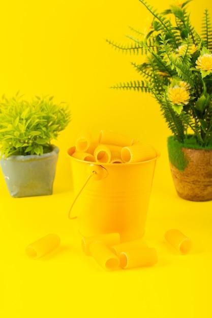 Widok Z Przodu Makaron Wewnątrz Kosza Uformowany Surowy Wewnątrz żółty Kosz Wraz Z Roślinami Na żółtym Tle Posiłek Włoski Spaghetti Darmowe Zdjęcia