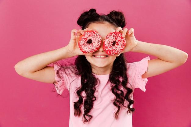 Widok z przodu mała dziewczynka bawi się z doughntus Darmowe Zdjęcia