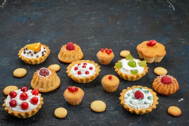 Widok Z Przodu Małe Pyszne Ciasta Ze śmietaną I świeżymi Owocami Na Ciemnym Biurku Słodkie Herbatniki Ciasto Cukier Darmowe Zdjęcia