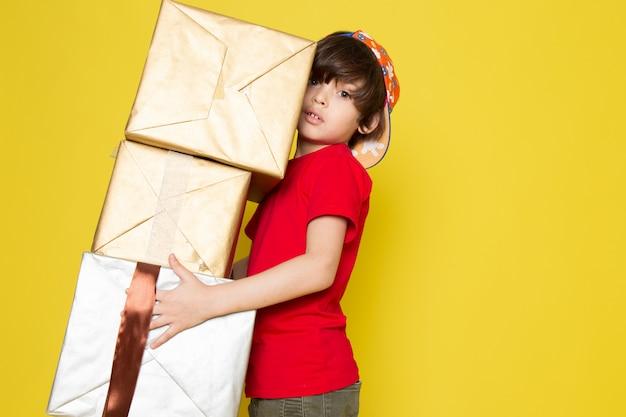 Widok Z Przodu Małego Chłopca W Czerwonej Czapce W Kolorowe T-shirty I Spodnie W Kolorze Khaki, Trzymającego Pudełko Na żółtym Tle Darmowe Zdjęcia