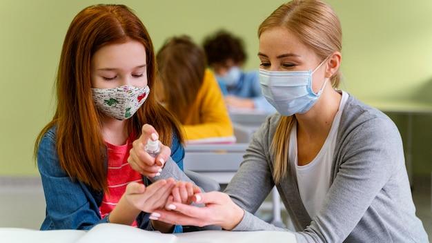 Widok Z Przodu Małej Dziewczynki Z Maską Medyczną Otrzymującą Od Nauczyciela środek Dezynfekujący Do Rąk Darmowe Zdjęcia