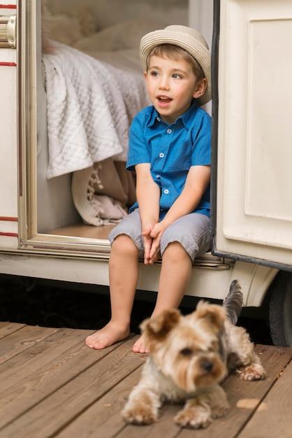 Widok Z Przodu Mały Chłopiec Siedzi Na Przyczepie Kempingowej Obok Uroczego Psa Darmowe Zdjęcia