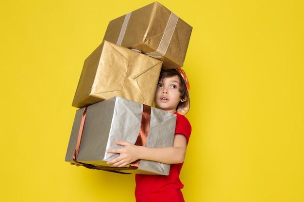 Widok Z Przodu Mały Chłopiec W Czerwonej Koszulce W Kolorowe Czapki I Spodnie W Kolorze Khaki, Trzymając Pudełka Na żółtym Tle Darmowe Zdjęcia
