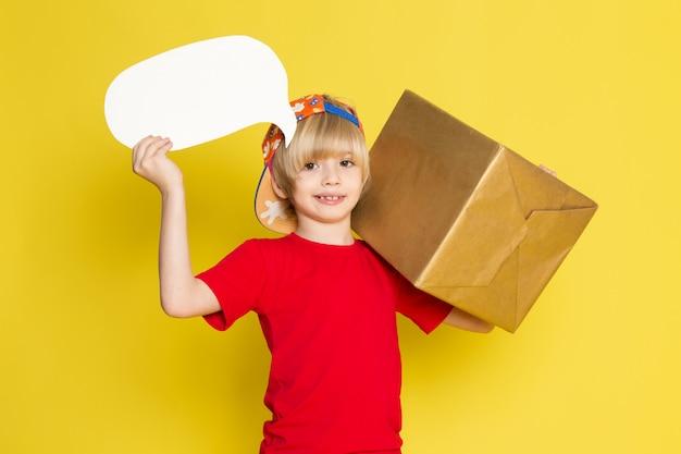 Widok Z Przodu Mały Chłopiec W Czerwonej Koszulce W Kolorowe Czapki I Szare Dżinsy Gospodarstwa Pudełko Na żółtym Tle Darmowe Zdjęcia
