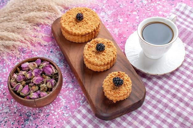 Widok Z Przodu Małych Ciastek Z Filiżanką Herbaty Na Różowej Powierzchni Darmowe Zdjęcia