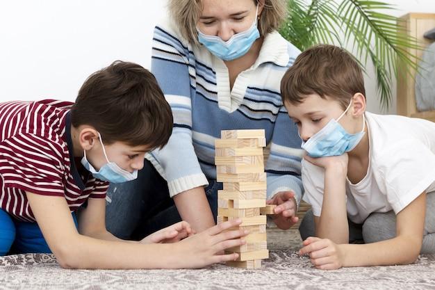 Widok Z Przodu Matki Gry Jenga Z Dziećmi W Domu Podczas Noszenia Masek Medycznych Premium Zdjęcia