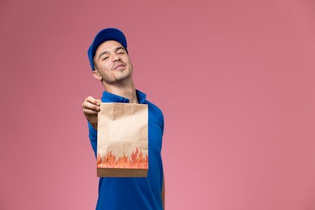 Widok Z Przodu Męski Kurier W Niebieskim Mundurze, Trzymając Pakiet żywności Na Różowej ścianie, Dostawa Usług Munduru Pracownika Darmowe Zdjęcia