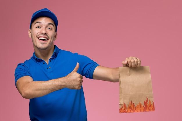 Widok Z Przodu Męski Kurier W Niebieskim Mundurze, Trzymając Pakiet żywności Uśmiechnięty Na Różowej ścianie, Jednolita Dostawa Pracy Serwisowej Darmowe Zdjęcia