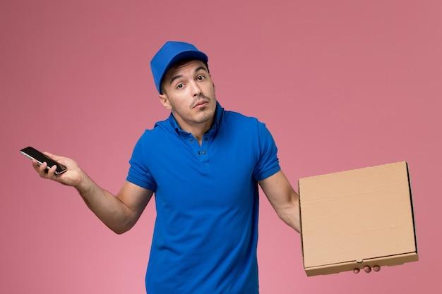 Widok Z Przodu Męski Kurier W Niebieskim Mundurze, Trzymając Pudełko Z Jedzeniem Z Telefonem Na Różowej ścianie, Pracownik W Mundurze Darmowe Zdjęcia
