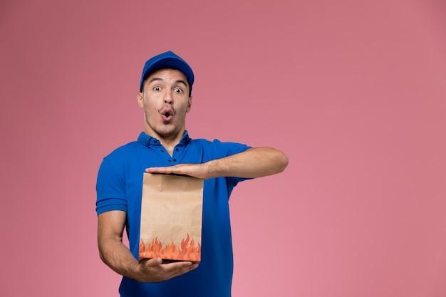 Widok Z Przodu Męski Kurier W Niebieskim Mundurze, Trzymający Paczkę Z Jedzeniem Z Zabawnym Wyrazem Na Różowej ścianie, świadczenie Usług W Mundurze Pracownika Darmowe Zdjęcia
