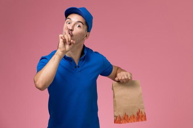Widok Z Przodu Męski Kurier W Niebieskim Mundurze Trzymający Pakiet żywności Z Prośbą O Milczenie Na Różowej ścianie, Jednolita Dostawa Usług Pracownika Darmowe Zdjęcia