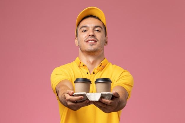 Widok Z Przodu Męski Kurier W żółtym Mundurze Dostarczający Filiżanki Kawy Dostawy Na Różowym Tle Darmowe Zdjęcia