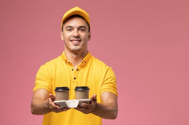 Widok Z Przodu Męski Kurier W żółtym Mundurze Dostarczający Kawowe Filiżanki Z Dostawą Na Jasnoróżowym Tle Darmowe Zdjęcia