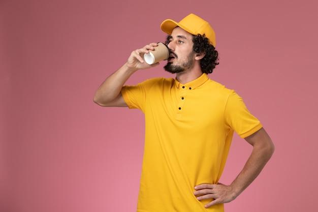 Widok Z Przodu Męski Kurier W żółtym Mundurze I Pelerynie Pijący Kawę Na Różowej ścianie Darmowe Zdjęcia