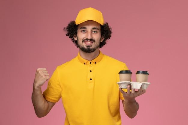 Widok Z Przodu Męski Kurier W żółtym Mundurze I Pelerynie, Trzymający Brązowe Filiżanki Do Kawy I Wiwatujący Na Różowej ścianie Darmowe Zdjęcia