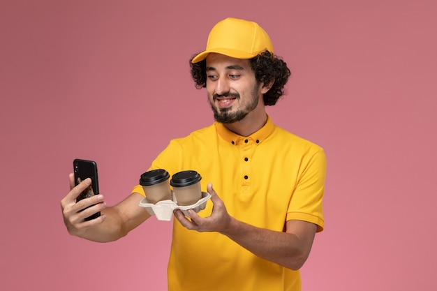 Widok Z Przodu Męski Kurier W żółtym Mundurze I Pelerynie Trzymający Brązowe Filiżanki Kawy Dostawy Robiąc Zdjęcie Na Różowej ścianie Darmowe Zdjęcia